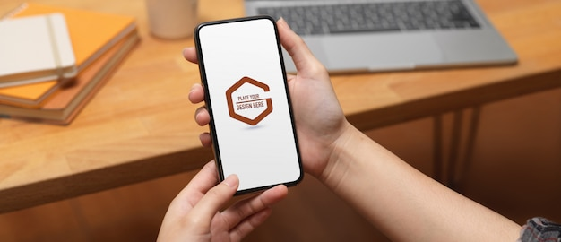 Male hand holding mockup of smartphone
