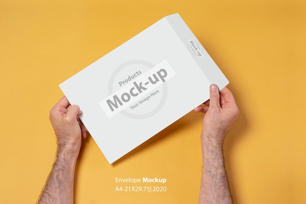 Male hand holding a paper envelope mock-up