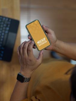 Мужская рука с помощью макета смартфона, сидя в офисной комнате
