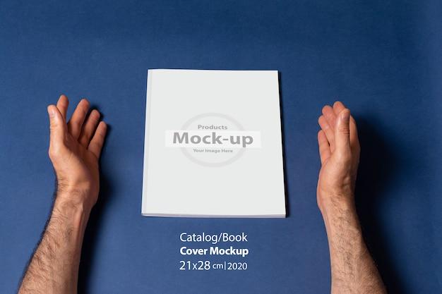 닫힌 카탈로그 또는 빈 표지와 잡지 주위 남성 손