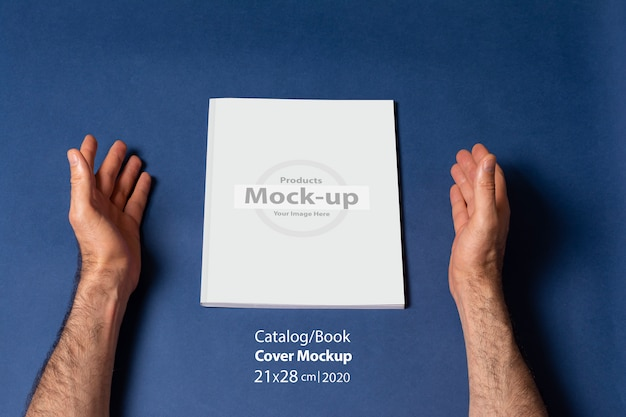 Male hands around a closed catalog or magazine with blank cover