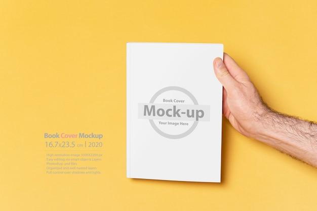 Мужские руки держат закрытую книгу с макетом пустой обложки
