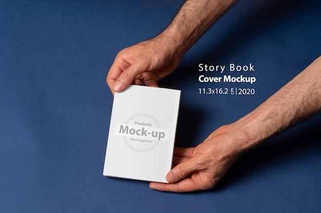 Мужские руки держат закрытую книгу-каталог с заглушкой