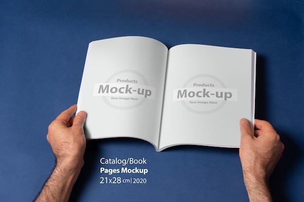 빈 페이지와 열린 책 또는 카탈로그를 들고 남자 손
