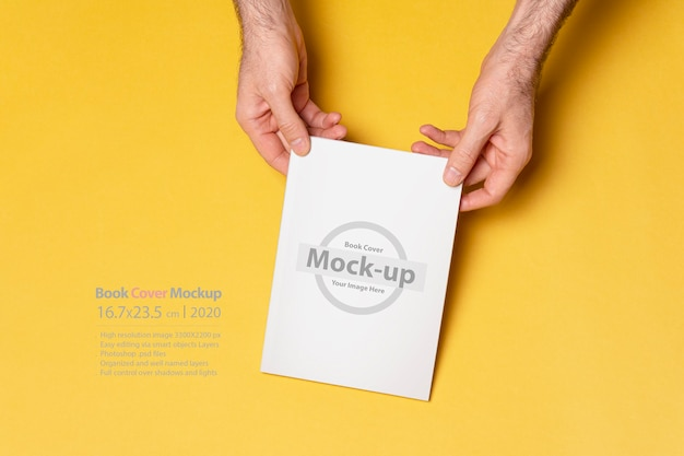 Male hands holding a closed book with blank cover mockup