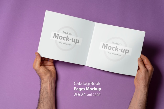 Male hands holding an opened catalog with blank pages on purple surface