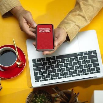 テーブルの上のラップトップとコーヒーカップとスマートフォンのモックアップを使用して男性の手