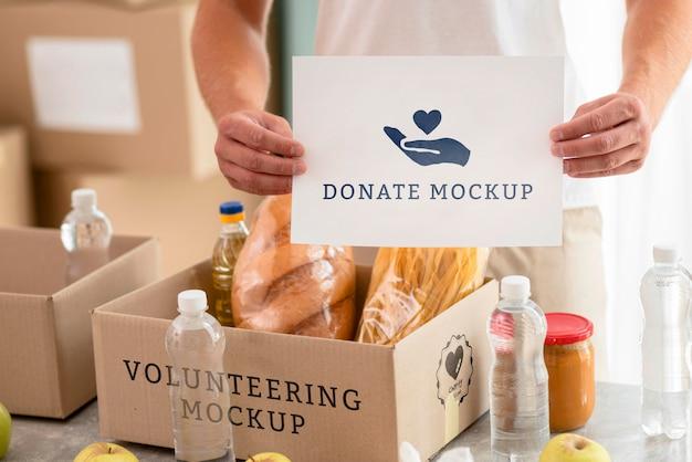 Волонтер-мужчина держит чистый лист бумаги с коробкой еды для пожертвования