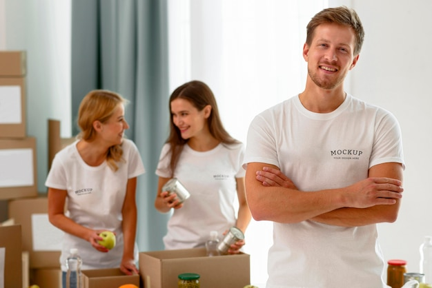 Male volunteer posing with arms crossed while colleagues prepare donation boxes