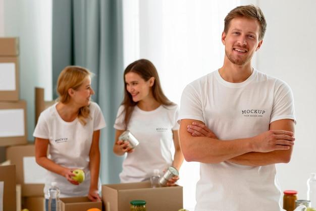 Мужчина-доброволец позирует со скрещенными руками, пока коллеги готовят коробки для пожертвований
