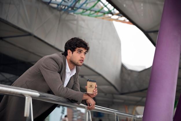 カップのモックアップとモダンな都会のきれいな空間で男