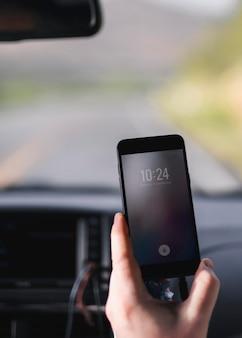 車の中で自分の携帯電話から時間をチェックする男