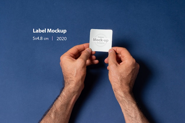 A man hands holding a small label mockup  in front of dark blue surface