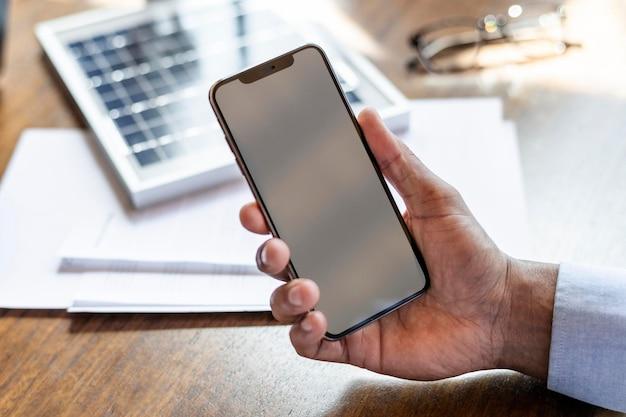 Человек, держащий пустой макет мобильного телефона