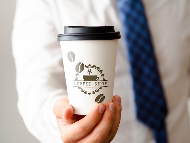 Мужчина держит чашку кофе макет