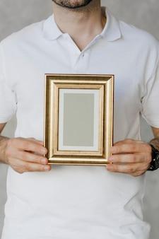 Человек, держащий макет золотой рамы