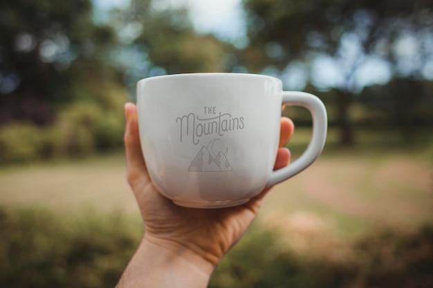 Мужчина держит макет белой кофейной чашки в парке