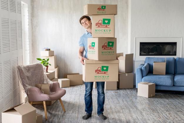 彼の新しい家の長い視野でオブジェクトとボックスを保持している男