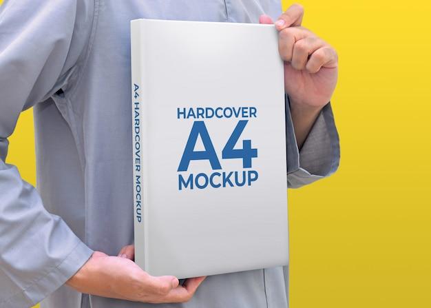 Мужчина держит книгу в твердом переплете формата а4 с цветным фоном макета