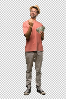 Man holding many bills inviting to come with hand. happy that you came