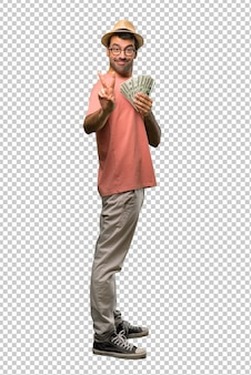 Man holding many bills smiling and showing victory sign