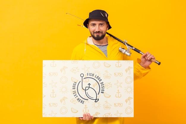 Man holding rod and mock-up horizontal card