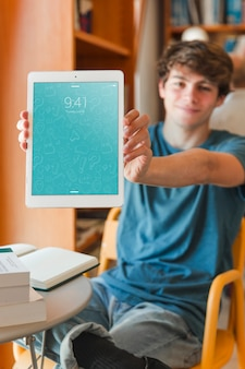 Man holding smartphone mockup in library