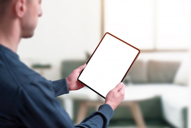Man holding tablet with isolated screen for mockup.