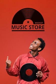 Мужчина держит виниловый диск для макета музыкального магазина