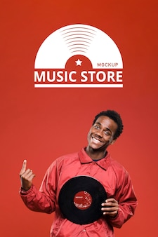 Man holding vinyl disk for music store mock-up and pointing up
