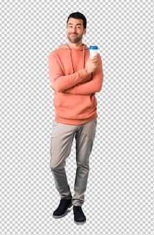 Man in a pink sweatshirt holding hot coffee in takeaway paper cup
