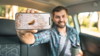 Man in car showing smartphone mockup