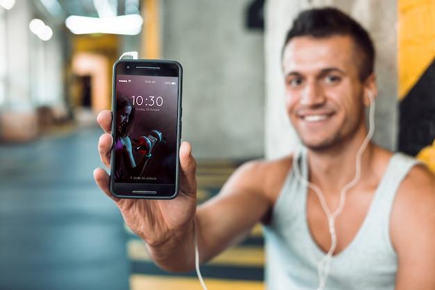 Мужчина в спортзале держит макет смартфона