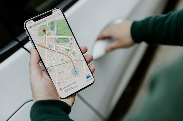 Человек смотрит на карту на своем смартфоне