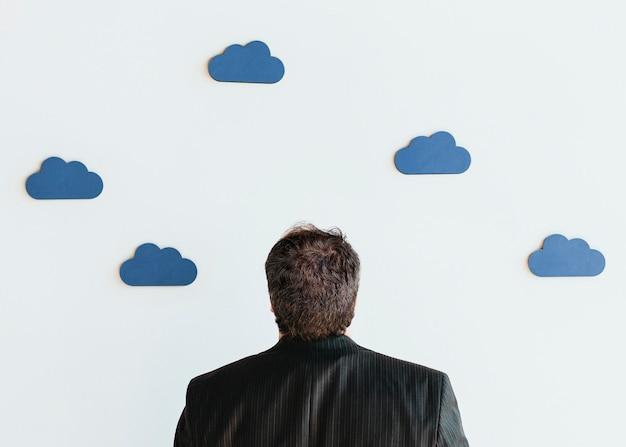 파란색 구름 아이콘 모형을 올려다 보는 남자
