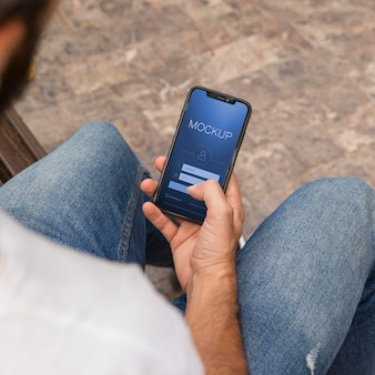 Человек на улице, читая книгу по телефону