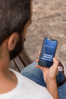 Человек на улице с телефоном с помощью приложения