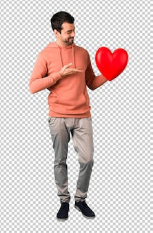 Man in a pink sweatshirt holding a big heart icon toy