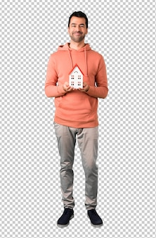 Man in a pink sweatshirt holding a little house