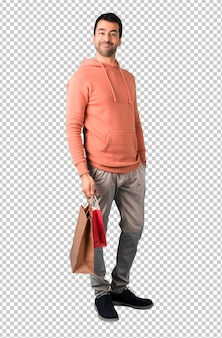 Man in a pink sweatshirt holding a lot of shopping bags while walking