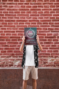 Man presenting poster mockup in front of brick wall