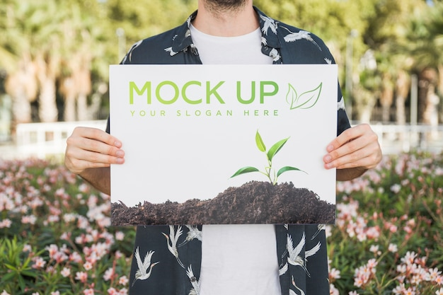 Man presenting poster mockup in front of park