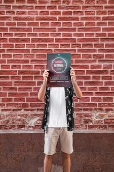 벽돌 벽 앞에서 포스터 이랑 제시하는 사람