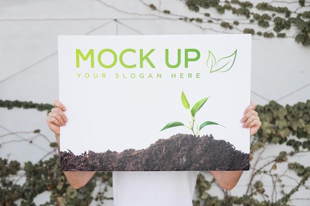 Man presenting poster mockup outdoors