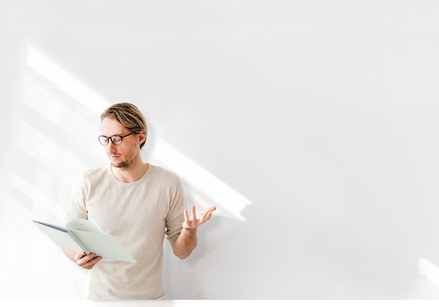 Man reading in front of white wall