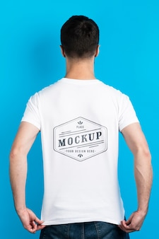 Человек показывает макет рубашки сзади