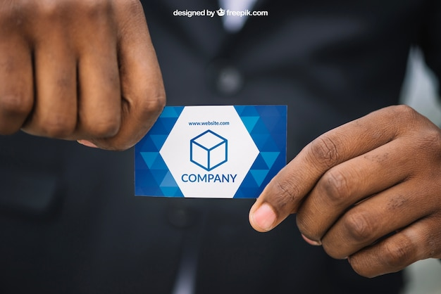 Man in suit holding business card mockup