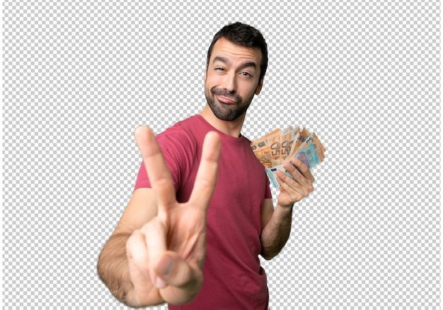 Man taking a lot of money smiling and showing victory sign
