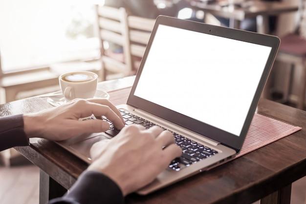 モックアップの分離画面でノートパソコンのキーボードで入力する男。コーヒーカップの横にあるコーヒーショップテーブル上のコンピューター。窓から光が入る