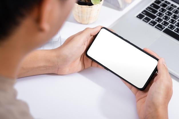 白いオフィスの机でスマートフォンの画面のモックアップを使用している男